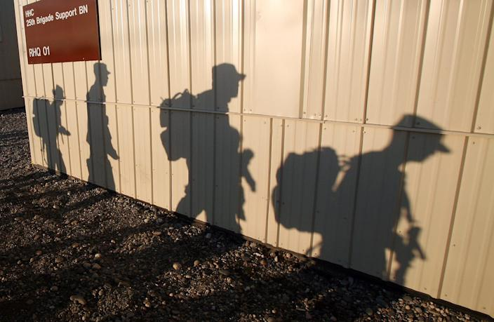 Soldiers with the 1-25th Stryker Brigade Combat Team Support Battalion cast shadows in the early morning sunrise as they prepare to deploy from Fort Wainwright in Fairbanks, Alaska, to Afghanistan May 7, 2011.