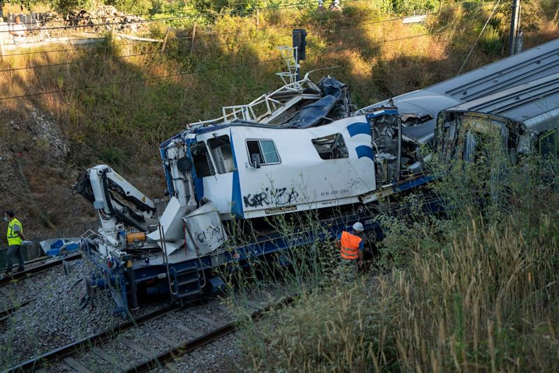 A wrecked maintenance vehicle rests by the tracks after an intercity passenger train collided with it (AP)
