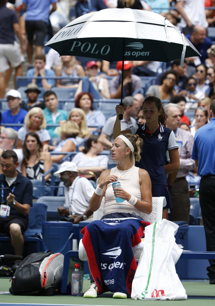 Victoria Azarenka, of Belarus, sits under and umbrella as the roof is closed during the third round of the U.S. Open tennis tournament against Sloane Stephens, Friday, Aug. 31, 2018, in New York. (AP Photo/Jason DeCrow)