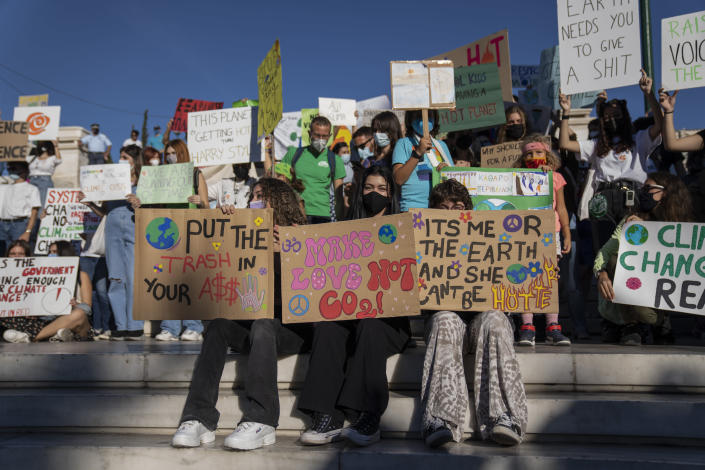 Students hold up banners during a rally in front of the parliament in Athens, on Friday, Sept. 24 2021. Hundreds gathered at Syntagma square to protest against global warming and climate change. (AP Photo/Petros Giannakouris)