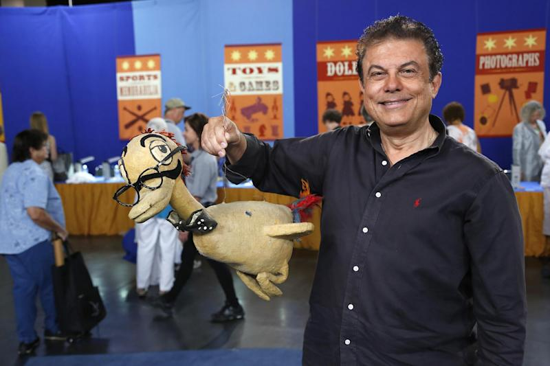 """This June 22, 2013 photo released by PBS shows a man named Joe holding a Max Brother prop duck during the taping of the popular appraisal show """"Antiques Roadshow,"""" in Anaheim, Calif. Top-rated PBS series """"Antiques Roadshow"""" is on the move, taping programs in eight U.S. cities for its upcoming 18th season. (AP Photo/PBS)"""