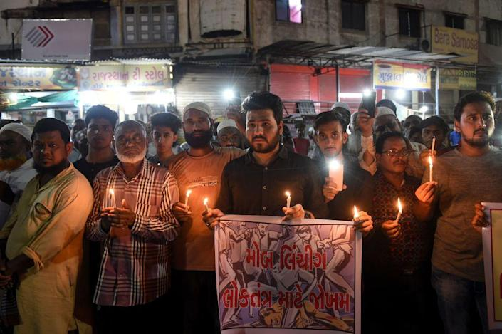 """Indian Muslims holding candles and posters as they participate in a protest against the mob lynching of Tabrez Ansari in the Jharkhand state, in Ahmedabad on June 27, 2019.<span class=""""copyright"""">SAM PANTHAKY/AFP via Getty Images</span>"""