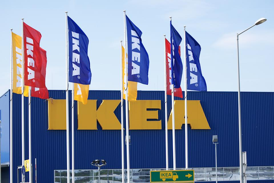 Graz, Austria - April 23, 2011: IKEA shop in Graz with red, blue and yellow flags fluttering in front of a building. Large yellow Ikea logo on facase. Small traffic sign showing direction for trucks. IKEA is producer of low price furniture located south of Stockholm in Sweden with branches all over the world.