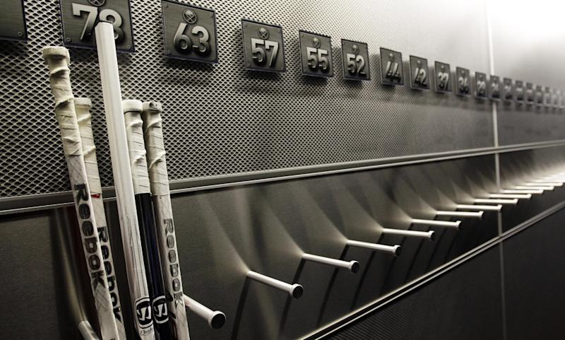 FILE - In this Sept. 25, 2012 file photo, a nearly empty hockey stick rack in the locker room of the Buffalo Sabres hockey team is shown during the NHL labor lockout in Buffalo, N.Y. The NHL lockout that's already wiped out the first three months of the season is taking its toll on Buffalo businesses. And it's no different in many of the NHL's 29 other markets. (AP Photo/David Duprey, File)