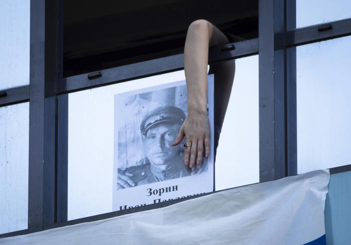 A woman hangs a portrait of her ancestor, a participant in World War II on the window of her apartment during Victory Day celebration in St. Petersburg, Russia, Saturday, May 9, 2020. Victory Day, the anniversary of the defeat of Nazi Germany in World War II, is Russia's most important secular holiday and this year's observance had been expected to be especially large because it is the 75th anniversary, but military parades in Russian cities and a mass procession called The Immortal Regiment were postponed as part of measures to stifle the spread of the virus. (AP Photo/Dmitri Lovetsky)