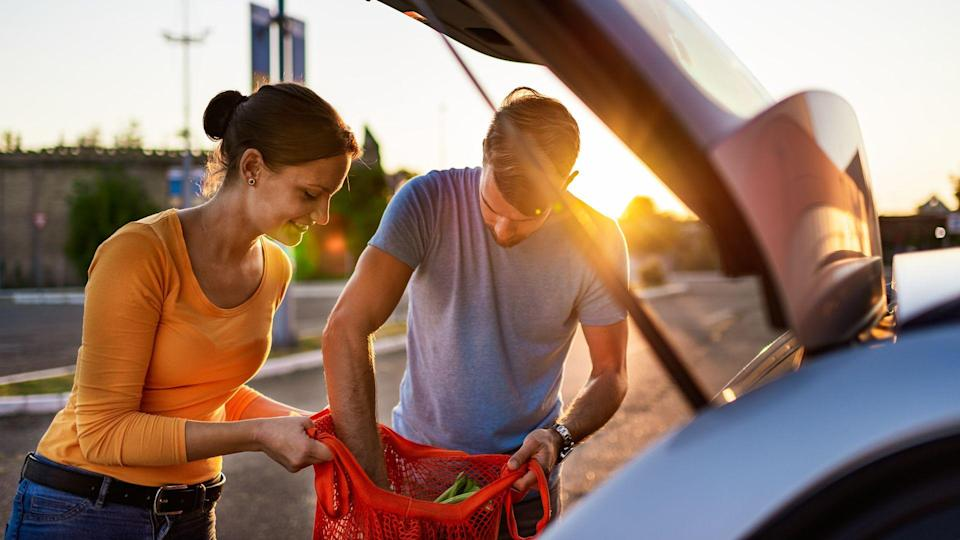 Young couple after grocery shopping on parking lot, putting groceries in car trunk.