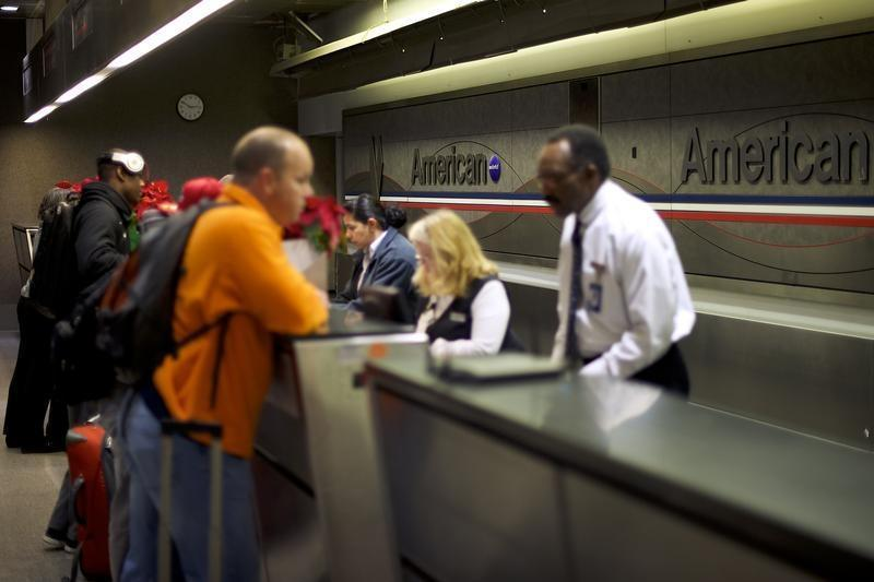 Employees check in travelers at the American Airlines check in counters at Philadelphia International Airport
