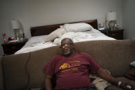 Mike Bishop sits in his bedroom on Thursday, Oct. 8, 2020, in Byram, Miss. In early July, Bishop was hit by COVID-19. Bishop was living alone at home, in a big suburban house. He'd wake up confused at 2 a.m. when Bonnie Bishop, his wife, wasn't beside him. (AP Photo/Wong Maye-E)