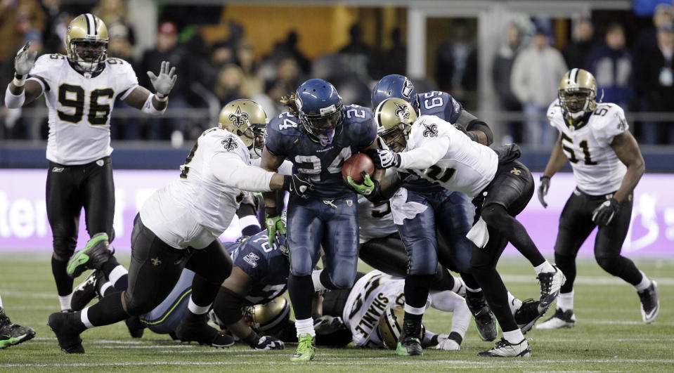 Seattle Seahawks' Marshawn Lynch (24) breaks away from a tackle by the New Orleans Saints defenders to score a touchdown in the second half of an NFL NFC wild card playoff football game, Saturday, Jan. 8, 2011, in Seattle. (AP Photo/Elaine Thompson)