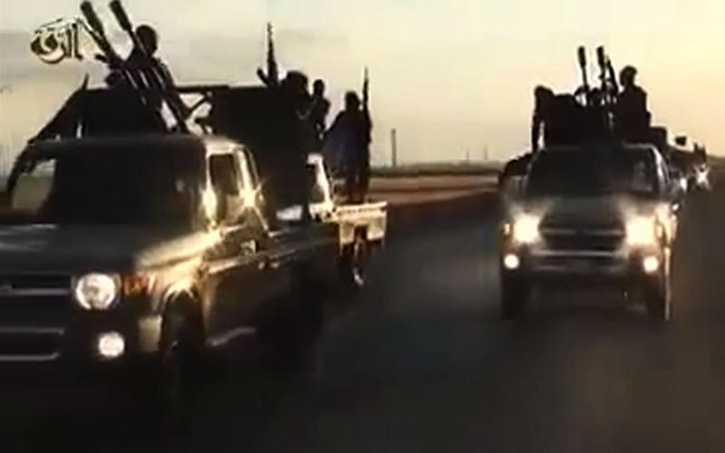 An image from a video released by Islamic State group's official Al-Raqqa site via YouTube on September 23, 2014, purportedly shows Islamic State (IS) recruits riding in armed trucks in an unknown location (AFP Photo/)