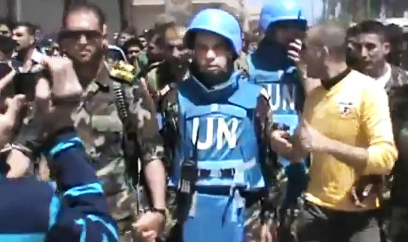 This image made from amateur video released by the Shaam News Network and accessed Sunday, April 22, 2012, purports to show a Free Syrian Army solider accompanying UN observers in Rastan town in Homs, Syria. U.N. cease-fire monitors toured a rebel-held town in central Syria Sunday with army defectors, while government troops pounded a Damascus suburb with artillery and heavy machine guns, activists said. (AP Photo/Shaam News Network via AP video) TV OUT, THE ASSOCIATED PRESS CANNOT INDEPENDENTLY VERIFY THE CONTENT, DATE, LOCATION OR AUTHENTICITY OF THIS MATERIAL