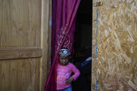 Chilean-born, three-year-old Benita, whose parents are Haitian, peers from her home's front door, in the Dignidad camp set up by migrants in Santiago, Chile, Thursday, Sept. 30, 2021. Benita's parents have not been able to renew their Chilean identity cards, which keeps them from being able to work legally. (AP Photo/Esteban Felix)