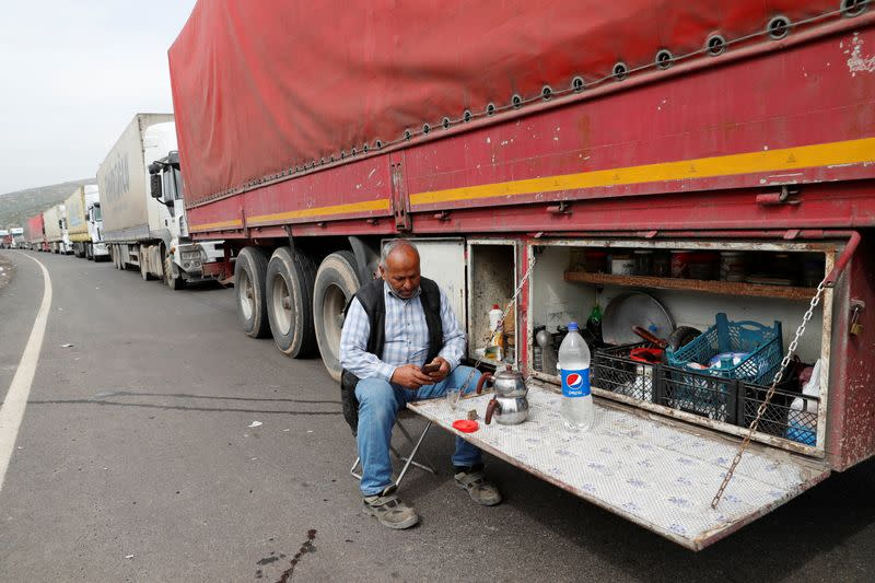 A driver sits next to his truck at the Cilvegozu border gate in Reyhanli