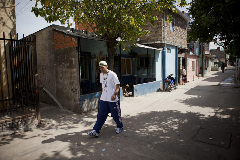 """Cristian Marcelo Reynoso, who works as a garbage collector, walks to work near the Virgin of Caacupe church in the Villa 21-24 slum in Buenos Aires, Argentina, Thursday, March 14, 2013. """"Four years ago, I was at my worst and I needed help. When the mass started he knelt down and washed my feet. It hit me hard. It was such a beautiful experience,"""" said Reynoso referring to then Archbishop Jorge Mario Bergoglio. Reynoso, 27, is trying to kick off an addiction to crack cocaine through the local church's rehab program. (AP Photo/Victor R. Caivano)"""