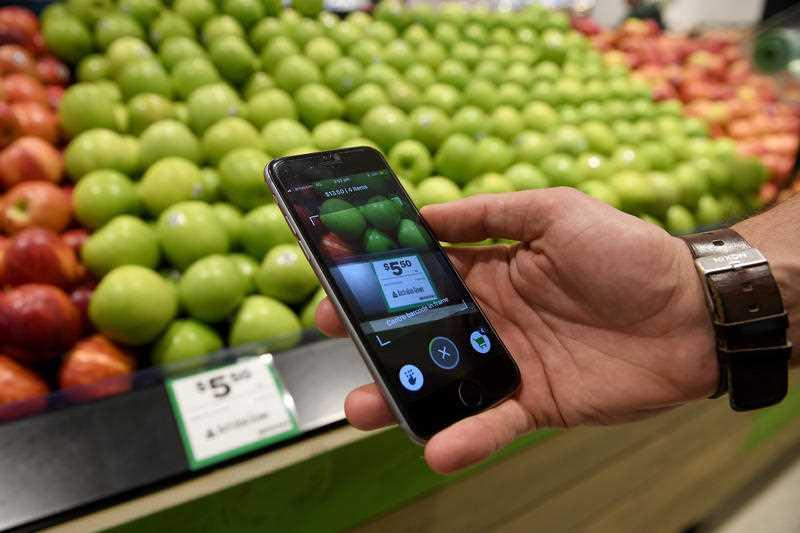 Woolworths' employee Bryn Rayfield uses the company's new Scan & Go app at the Double Bay store in Sydney.