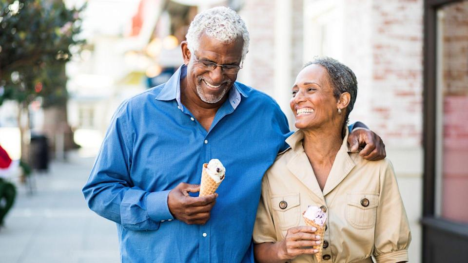 A senior african american couple enjoy an evening on the town with ice cream.