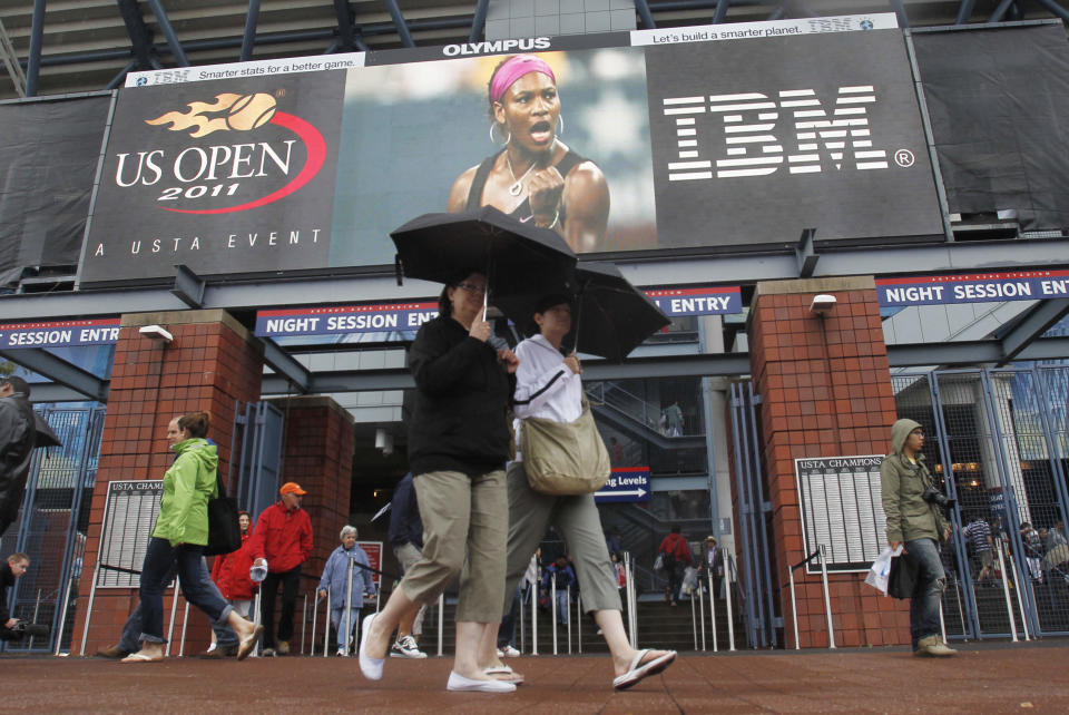 FILE - In this Sept. 6, 2011, file photo, fans walk near an entrance to Arthur Ashe Stadium during the U.S. Open tennis tournament in New York. Spectators will not be required to wear masks or show proof of their vaccination status to attend matches at the U.S. Open when the tennis tournament returns at full capacity next week, one year after all fans were banned from the event because of the coronavirus pandemic. (AP Photo/Mike Groll, File)