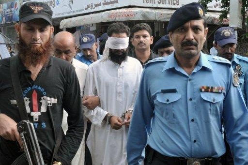 Pakistani policemen escort Islamic cleric Hafiz Mohammed Khalid Chishti upon his arrival at a court in Islamabad on September 2. The cleric who submitted evidence against a Christian girl accused of blasphemy has been arrested on suspicion of evidence-tampering and desecrating the Koran, police said