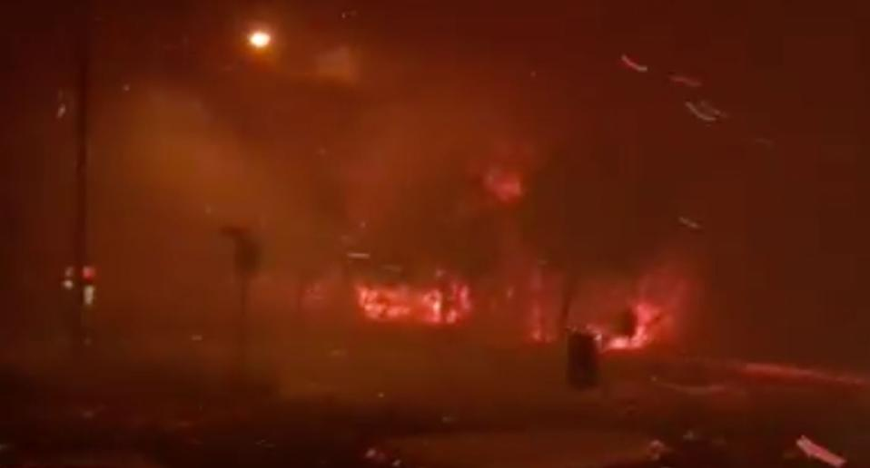 Bushfire in Queensland shoots angry red flames across a street.