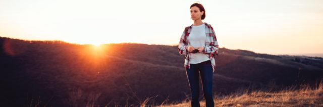middle-aged woman in a flannel shirt and jeans standing on a hill during sunset looking out