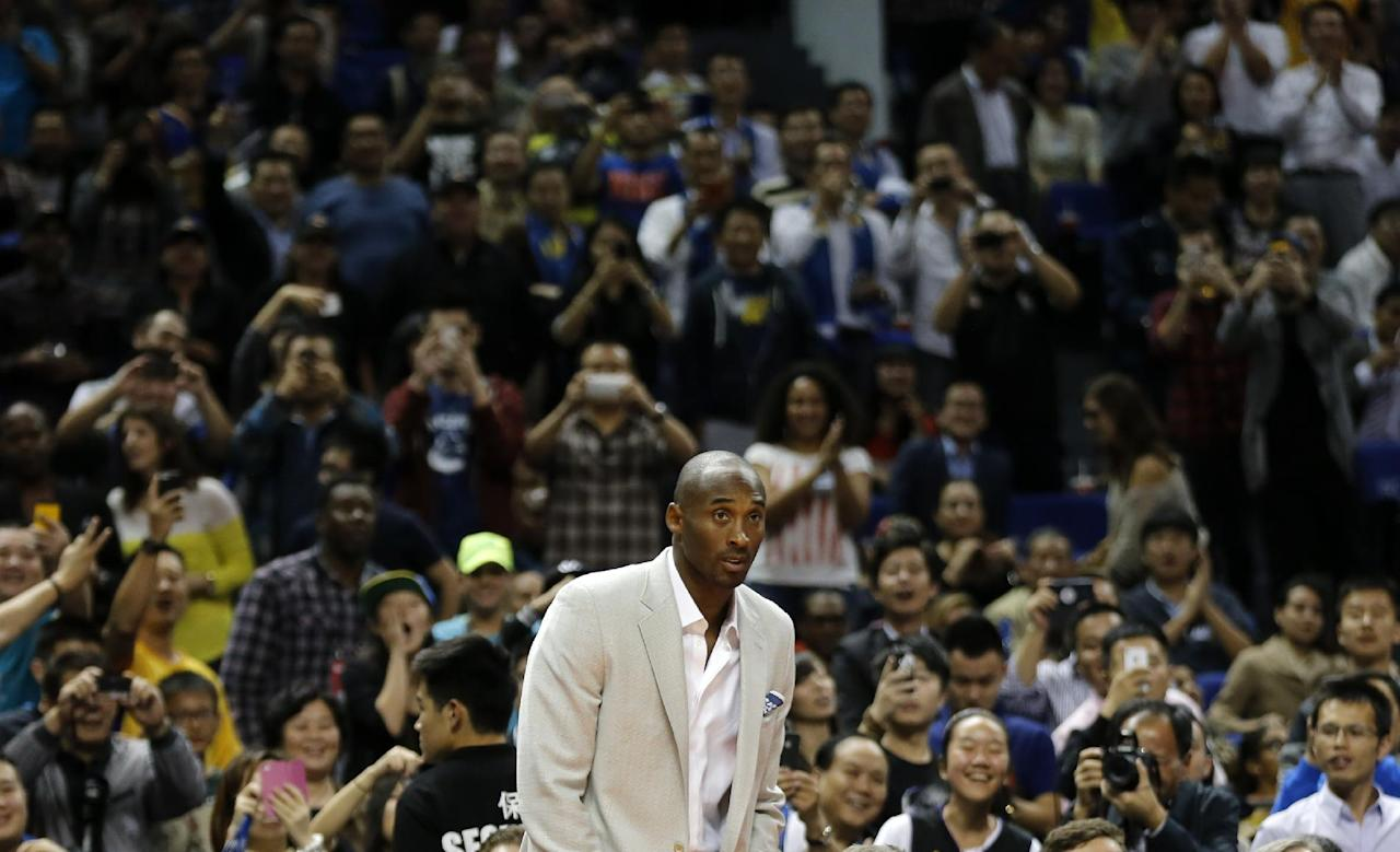 Kobe Bryant of the Los Angeles Lakers arrives onto the court during a 2013-2014 NBA preseason game between Los Angeles Lakers and Golden State Warriors at Mercedes-Benz Arena in Shanghai, China, Friday, Oct. 18, 2013. (AP Photo/Eugene Hoshiko)
