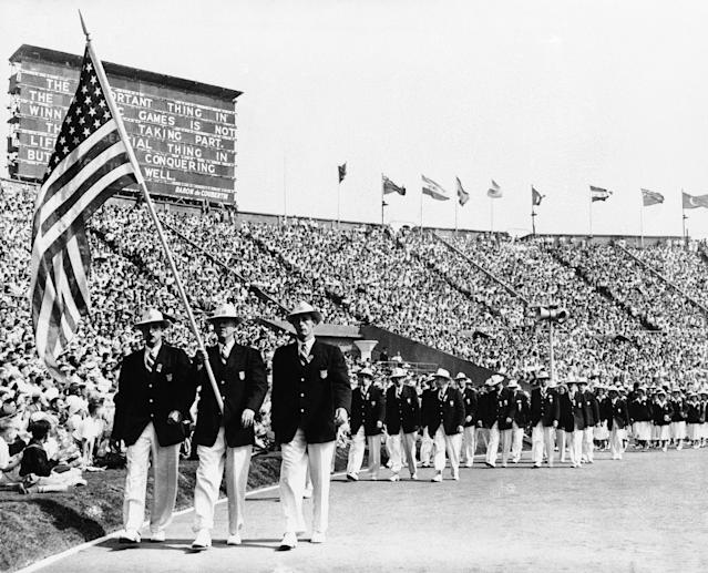 Ralph Craig, center, of Albany, N.Y., who won the 100- and 200-meter dashes in the 1912 Olympic games in Stockholm, and is a member of the U.S. Olympic Yachting team in the 1948 games, bears the American flag in the parade of the nations at the opening of the Olympic games in London's Wembley Stadium, July 29, 1948. (AP Photo)