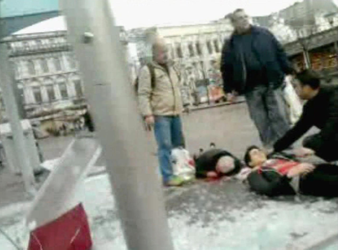In this image taken from video, injured people are treated by members of the public, as they lay injured in the moments immediately following a grenade attack in the city center of Liege, Belgium, Tuesday, Dec. 13, 2011. A man armed with hand grenades and guns opened fire in the crowded center of the Belgian city of Liege, Tuesday, killing at least four people and wounding some 75, an official said. This amateur video was filmed on a mobile phone by a man who was nearby when the grenades exploded. (AP Photo/Wissam Anabtawi, APTV) TV OUT