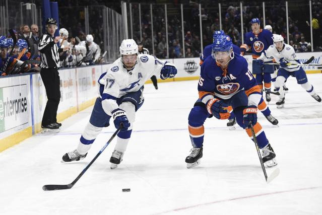 Tampa Bay Lightning's Victor Hedman (77) and New York Islanders' Cal Clutterbuck (15) skate to the puck during the first period of an NHL hockey game Friday, Feb. 1, 2019, in Uniondale, N.Y. (AP Photo/Kathleen Malone-Van Dyke)