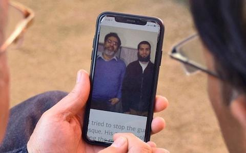 Relatives look the pictures of Pakistani citizen Rashid Naeem, and his son Talha Naeem - Credit: AP