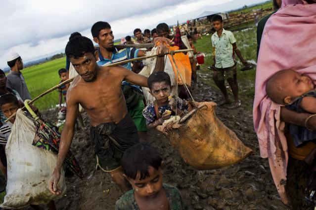 <p>A Rohingya ethnic minority from Myanmar carries a child in a sack and walks through rice fields after crossing over to the Bangladesh side of the border near Cox's Bazar's Teknaf area, Friday, Sept. 1, 2017. (Photo: Bernat Armangue/AP) </p>