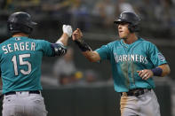 Seattle Mariners' Dylan Moore, right, is congratulated by Kyle Seager after scoring a run against the Oakland Athletics during the third inning of a baseball game in Oakland, Calif., Monday, Sept. 20, 2021. (AP Photo/Jeff Chiu)