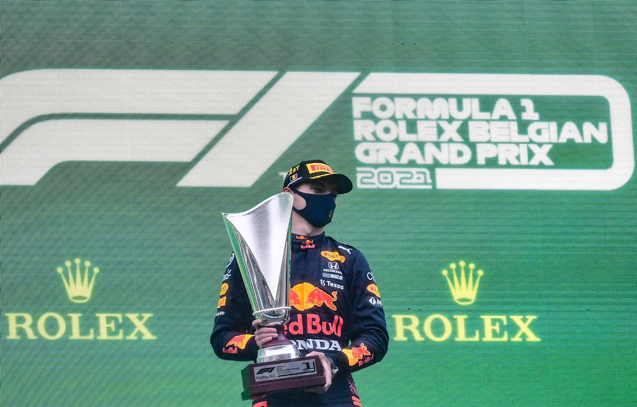 Max Verstappen poses with the trophy as he celebrates his first place on the podium at the Spa-Francorchamps circuit.