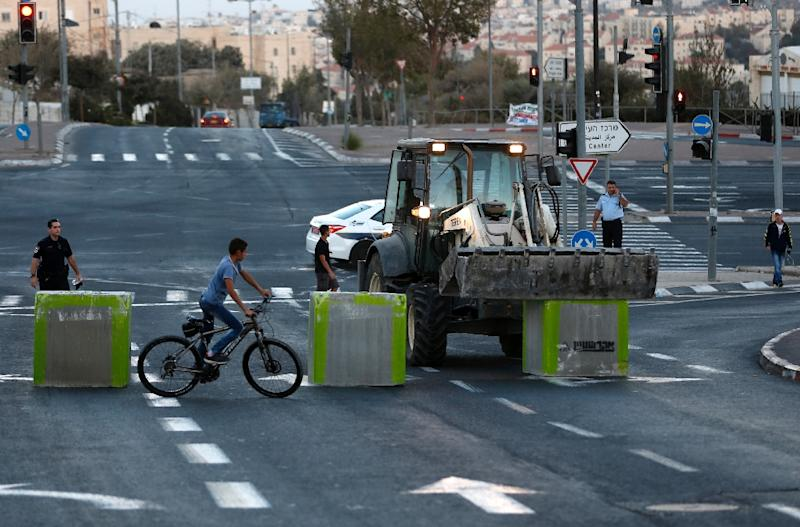 Israeli policeman stand guard as cement blocks are placed by Israeli security forces on a road linking the Arab east Jerusalem neighbourhood of Beit Hanina and West Jerusalem, on October 11, 2016, ahead of Yom Kippur (AFP Photo/Ahmad Gharabli)