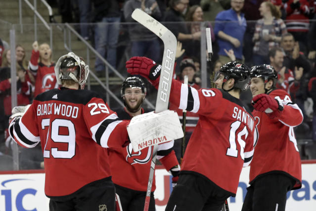New Jersey Devils players celebrate with goaltender MacKenzie Blackwood (29) after defeating the Arizona Coyotes 2-1 in a shootout during an NHL hockey game, Saturday, March 23, 2019, in Newark, N.J. (AP Photo/Julio Cortez)