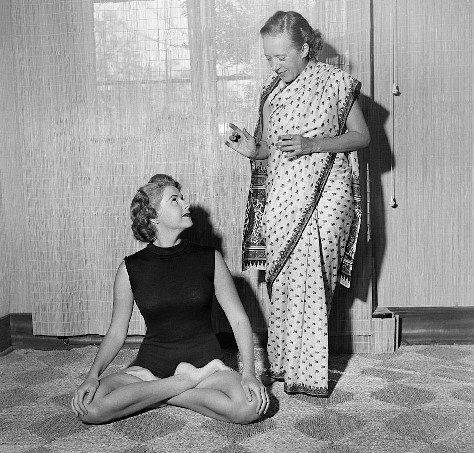 "<p>In the 1950s, yoga became more popular in the US when <a href=""https://www.yogajournal.com/yoga-101/yogas-trip-america/"" rel=""nofollow noopener"" target=""_blank"" data-ylk=""slk:Walt and Magana Baptiste"" class=""link rapid-noclick-resp"">Walt and Magana Baptiste</a> opened a West Coast yoga studio. Yogi Indra Devi also opened a popular yoga studio in Hollywood that attracted a lot of attention, which is where this photo was taken. <br></p>"