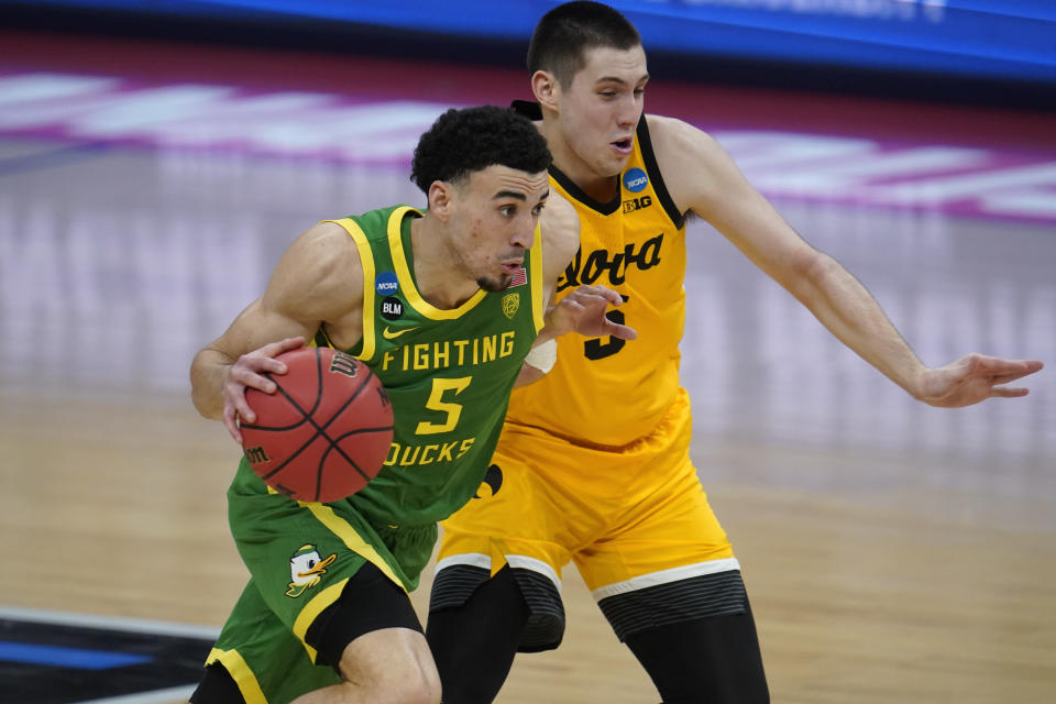 Oregon guard Chris Duarte (5) drives on Iowa guard CJ Fredrick during the second half of a men's college basketball game in the second round of the NCAA tournament at Bankers Life Fieldhouse in Indianapolis, Monday, March 22, 2021. (AP Photo/Paul Sancya)