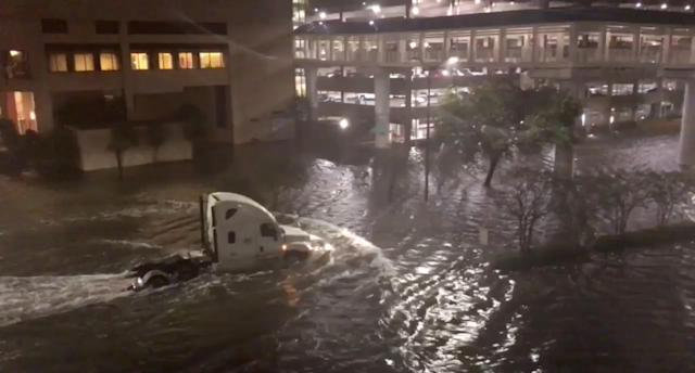 <p>A vehicle drives through a flooded street in Mobile, Alabama, U.S., October 8, 2017, in this still image taken from a video obtained from social media. (Photo: Michael Schubert via Reuters) </p>