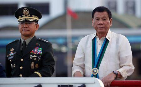 Philippine President Rodrigo Duterte reviews troops next to armed forces chief General Eduardo Ano during the Armed Forces anniversary celebration at Camp Aguinaldo in Quezon city