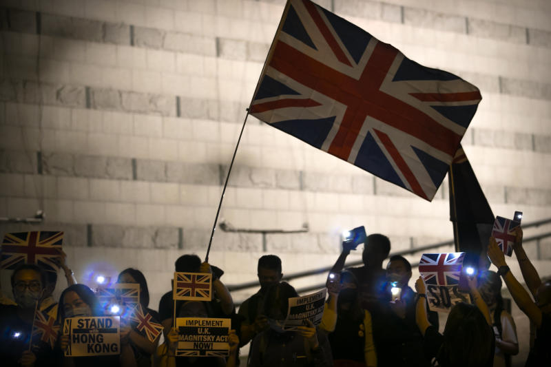 Demonstrators wave a British flag during a rally outside of the British Consulate in Hong Kong, Wednesday, Oct. 23, 2019.  Some hundreds of Hong Kong pro-democracy demonstrators have formed a human chain at the British consulate to rally support for their cause from the city's former colonial ruler. (AP Photo/Mark Schiefelbein)