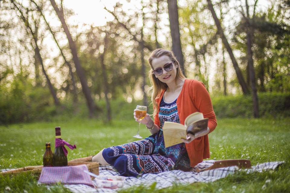 Beautiful young woman having a picnic, relaxing in nature, and reading a book on a sunny day