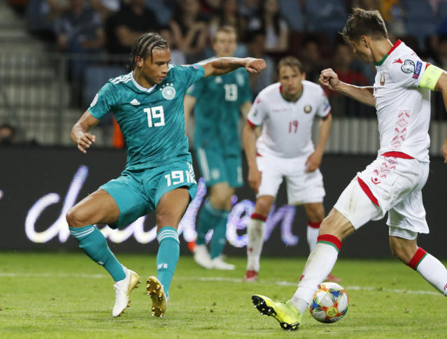 Germany's Leroy Sane, left, fights for the ball with Belarus' Alyaksandr Martynovich during the Euro 2020 group C qualifying soccer match between Belarus and Germany at the Borisov-Arena in Borisov, Belarus, Saturday, June 8, 2019. (AP Photo/Mindaugas Kulbis)