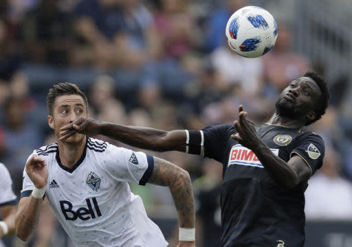 Philadelphia Union's C.J. Sapong, right, and Vancouver Whitecaps' Jose Aja chase the ball during the first half of an MLS soccer match, Saturday, June 23, 2018, in Chester, Pa. (AP Photo/Matt Slocum)