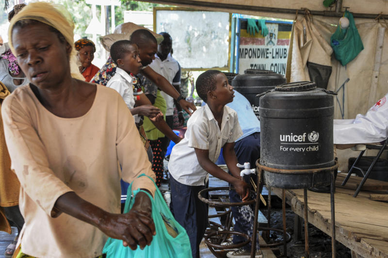 People coming from Congo wash their hands with chlorinated water to prevent the spread of infection, at the Mpondwe border crossing with Congo, in western Uganda Friday, June 14, 2019. In Uganda, health workers had long prepared in case the Ebola virus got past the screening conducted at border posts with Congo and earlier this week it did, when a family exposed to Ebola while visiting Congo returned home on an unguarded footpath. (AP Photo/Ronald Kabuubi)