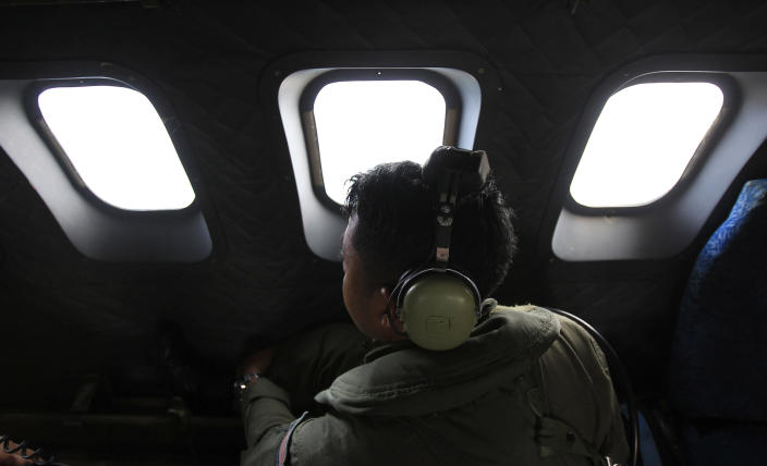 A crew member of a Royal Malaysian Air Force CN-235 aircraft looks out the window during a search and rescue operation for the missing Malaysia Airlines plane over the Straits of Malacca, Thursday, March 13, 2014. Planes sent Thursday to check the spot where Chinese satellite images showed possible debris from the missing Malaysian jetliner found nothing, Malaysia's civil aviation chief said, deflating the latest lead in the six-day hunt. The hunt for the missing Malaysia Airlines flight 370 has been punctuated by false leads since it disappeared with 239 people aboard about an hour after leaving Kuala Lumpur for Beijing early Saturday. (AP Photo/Lai Seng Sin)