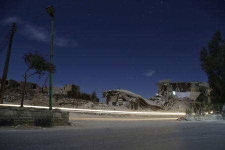 Damaged buildings are pictured at night in the rebel-controlled area of Maaret al-Numan town in Idlib province, Syria December 26, 2015. Picture taken with long exposure. REUTERS/Khalil Ashawi