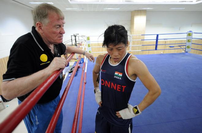"TO GO WITH AFP STORY Oly-2012-India-box-women,FEATURE by Rachel O'Brien In a picture taken on April 19, 2012, coach Charles Atkinson (L) speaks with Indian boxer MC Mary Kom during a training session for the 2012 London Olympics at the Balewadi Sports Complex in Pune. From her beginnings as a poor farmers' daughter in a remote and troubled corner of India, ""Magnificent Mary"" has fought her way up to become five-times world boxing champion. The mum-of-two is now tipped as her country's best bet to win gold at London 2012 -- a position few could envisage when she began learning to box. AFP PHOTO/ Punit PARANJPEPUNIT PARANJPE/AFP/GettyImages"