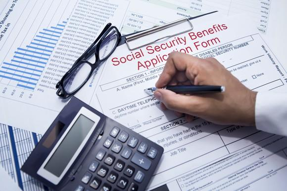 A person filling out a Social Security application form.