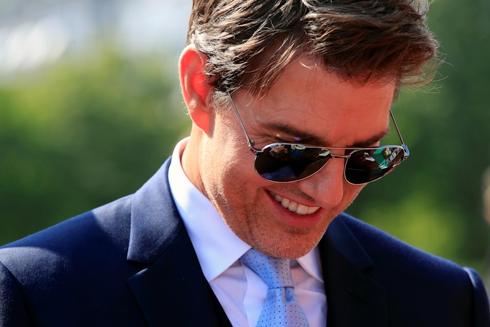 Cast member Tom Cruise signs autographs as he arrives for the world premiere of