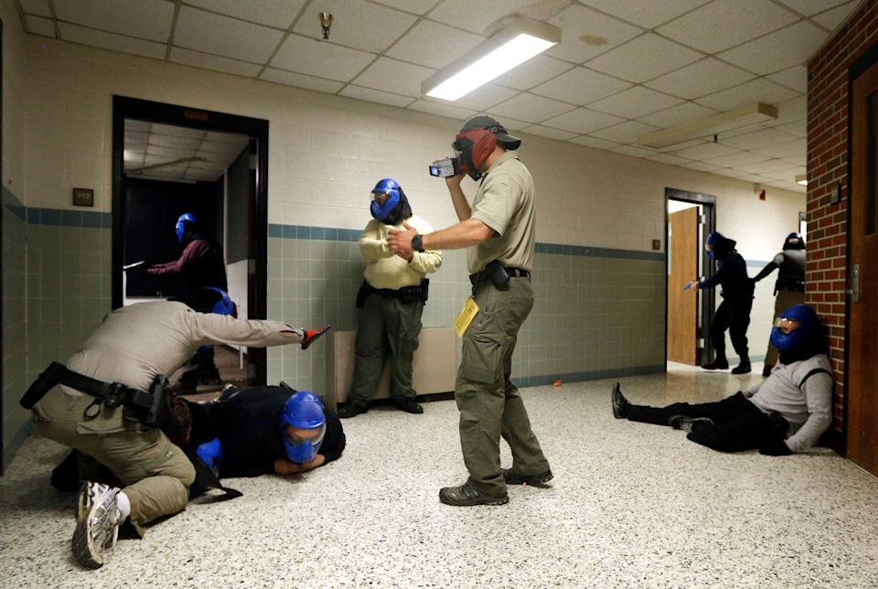 In this Aug. 13, 2013, photo, FBI instructor Mike Sotka, center, films local police officers as they participate in an active shooter drill in a college classroom building in Salisbury, Maryland, as part of an FBI program that teaches local law enforcement best practices for responding to mass shootings. The goal is to promote a standardized strategy as multiple local police departments — invariably the first officers at any scene — respond to the same shooting.