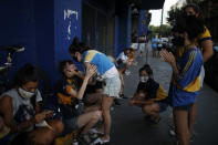 Fans mourn the death of Diego Maradona at the entrance of the Boca Juniors stadium, known as La Bombomera, in Buenos Aires, Argentina, Wednesday, Nov. 25, 2020. The Argentine soccer great who was among the best players ever and who led his country to the 1986 World Cup title before later struggling with cocaine use and obesity, died from a heart attack on Wednesday at his home in Buenos Aires. He was 60. (AP Photo/Natacha Pisarenko)